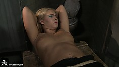 With her hands and feet tied, the blonde has Kathia gently spanking her pussy