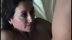 Busty brunette cougar reveals her oral skills and enjoys a deep fucking on the bed